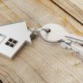 Hauskauf mit Haus als Anhänger am Schlüssel auf Holz