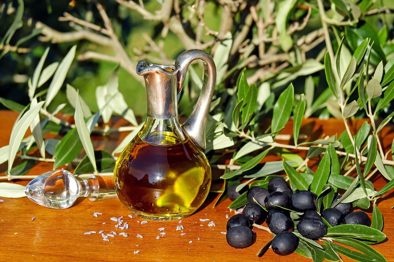 Dzbanek oliwy i oliwki na stole w ogrodzie