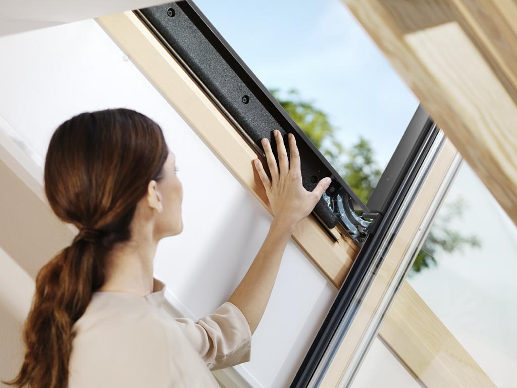 Kobieta spoglądająca na drewniane okno